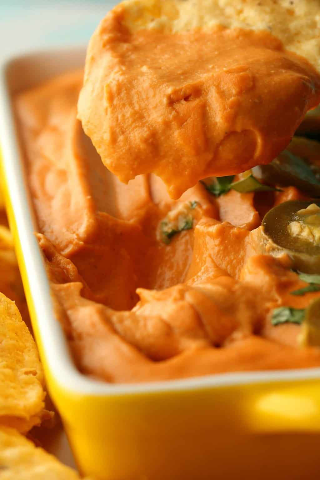 A corn chip dipping into a yellow and white serving dish of vegan queso.