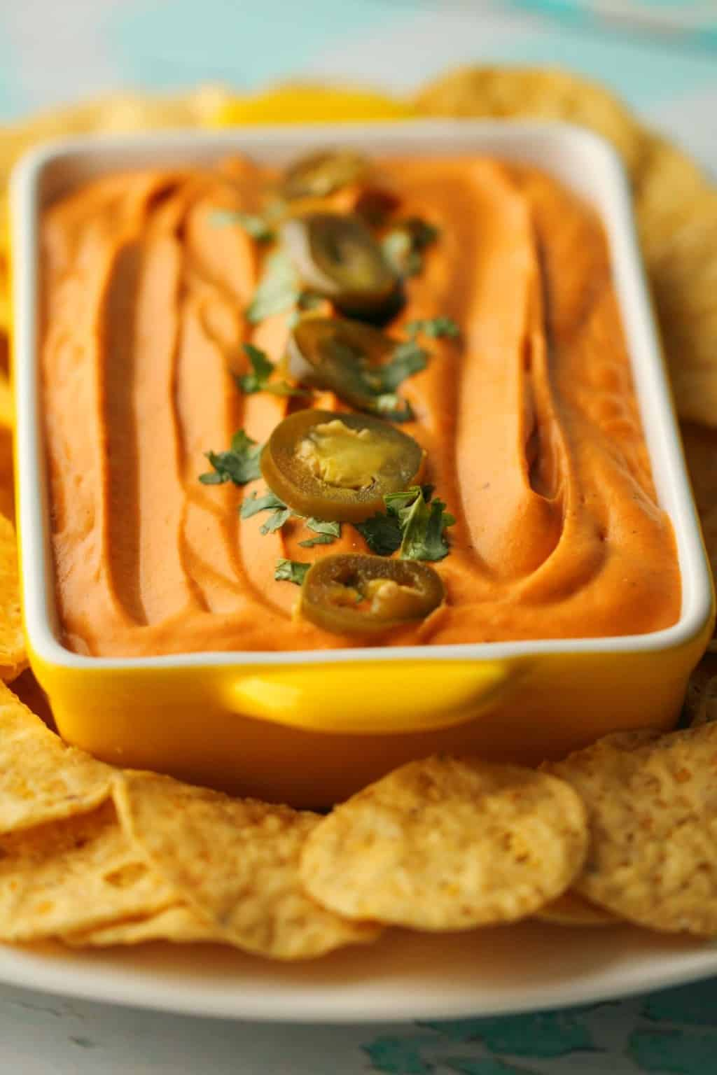 Vegan Queso in a yellow and white serving bowl surrounded by corn chips.