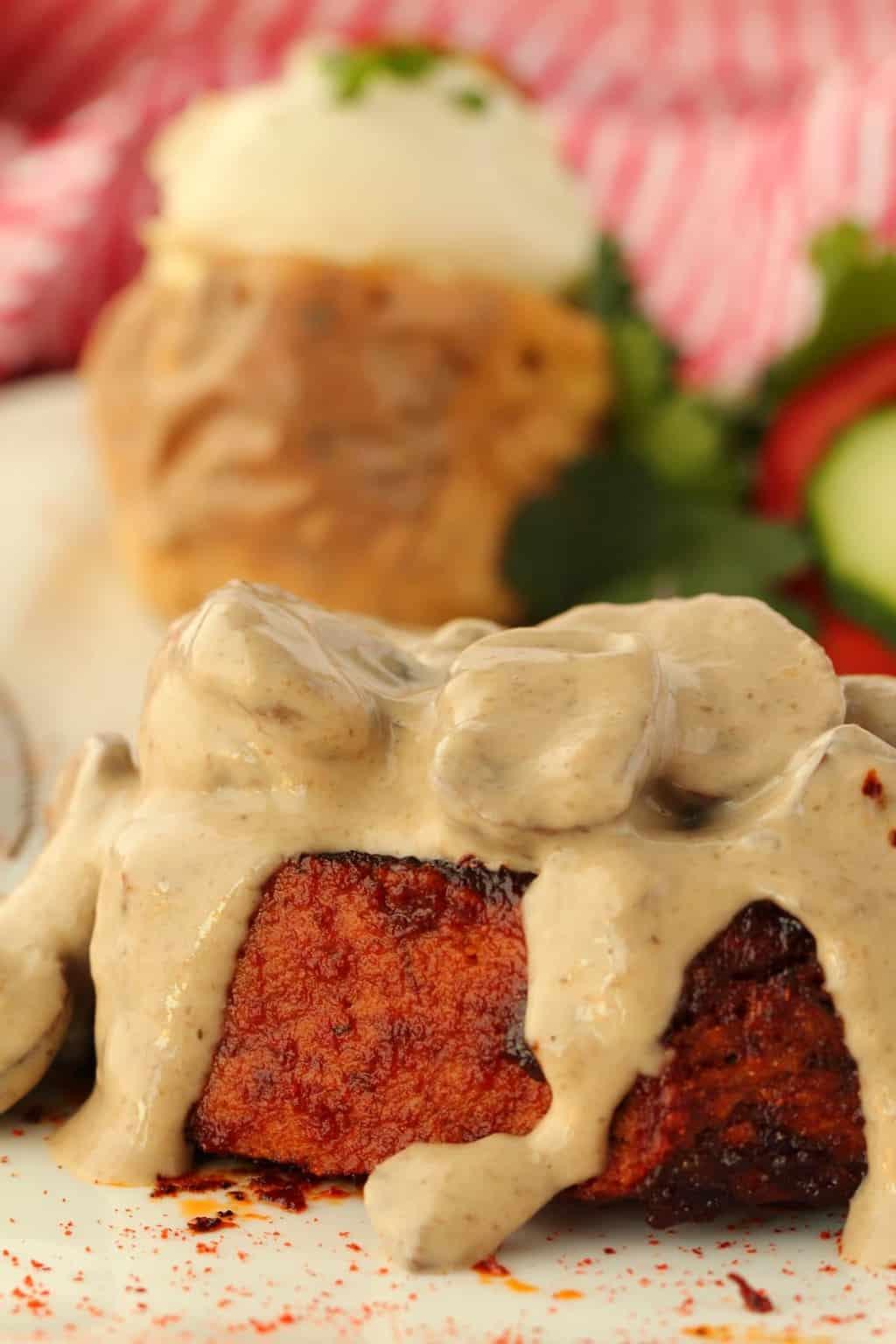 Vegan Steak covered in mushroom sauce on a white plate.