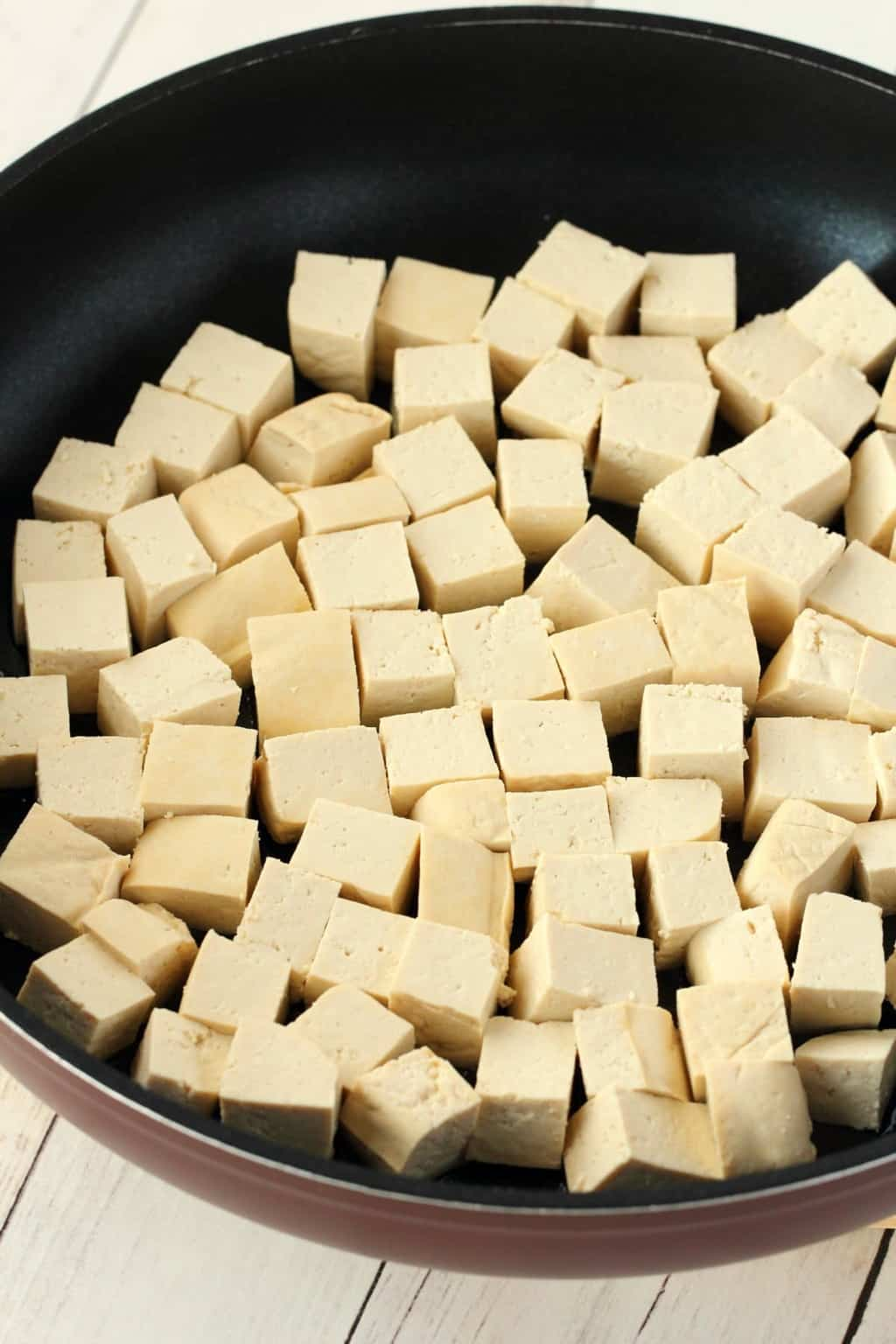 Cubes of tofu in a frying pan.