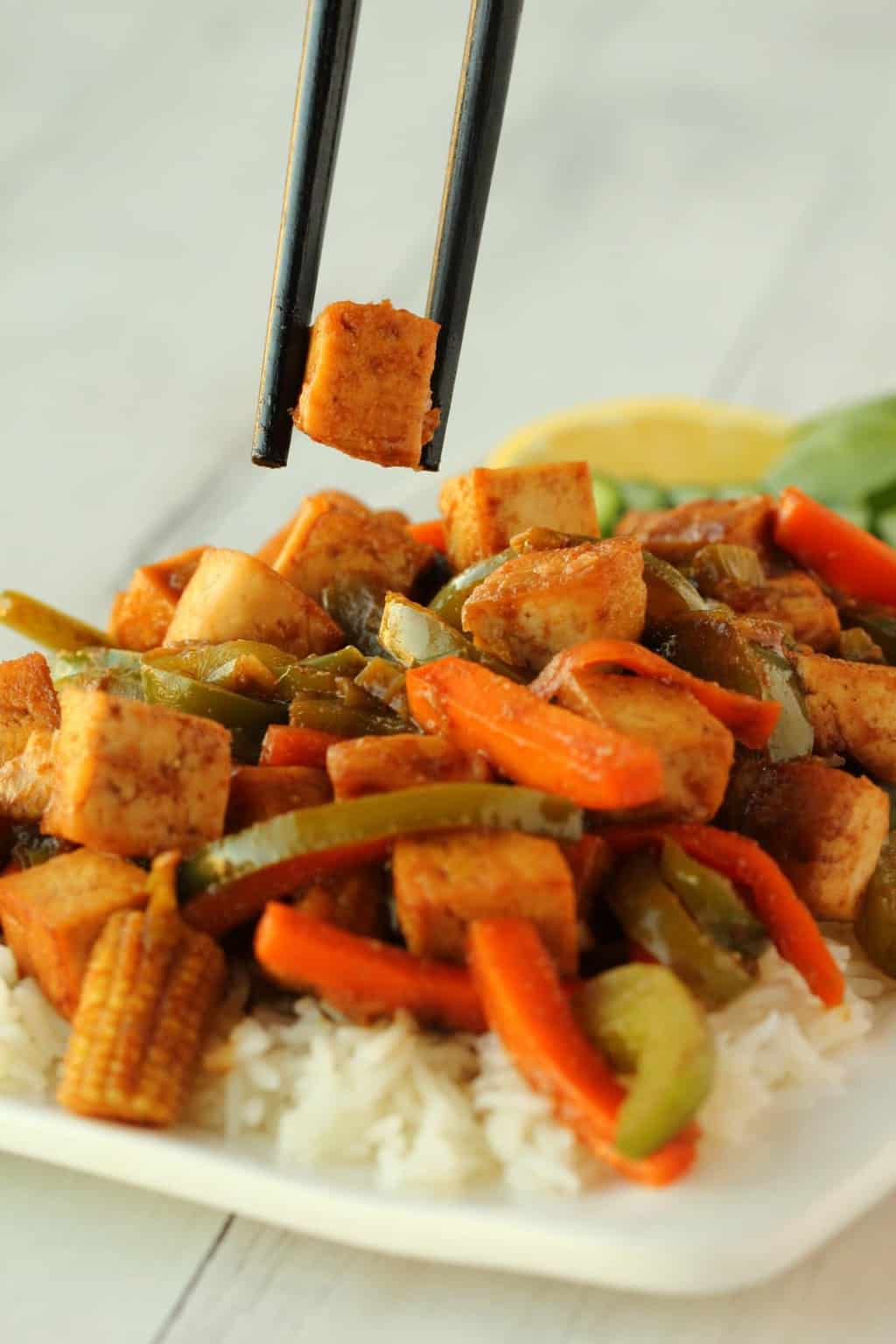 Chopsticks lifting a piece of tofu from a vegan tofu stir fry served over rice on a white plate.