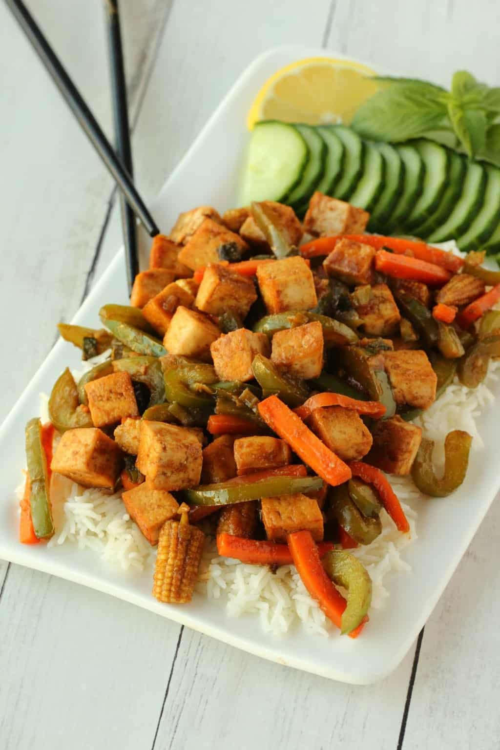 Vegan Tofu Stir Fry served over rice on a white plate.
