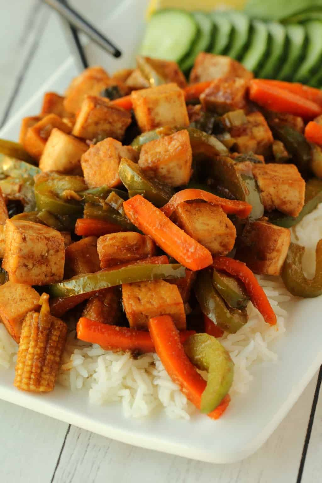 Vegan Tofu Stir Fry served over rice on a white plate with chopsticks.