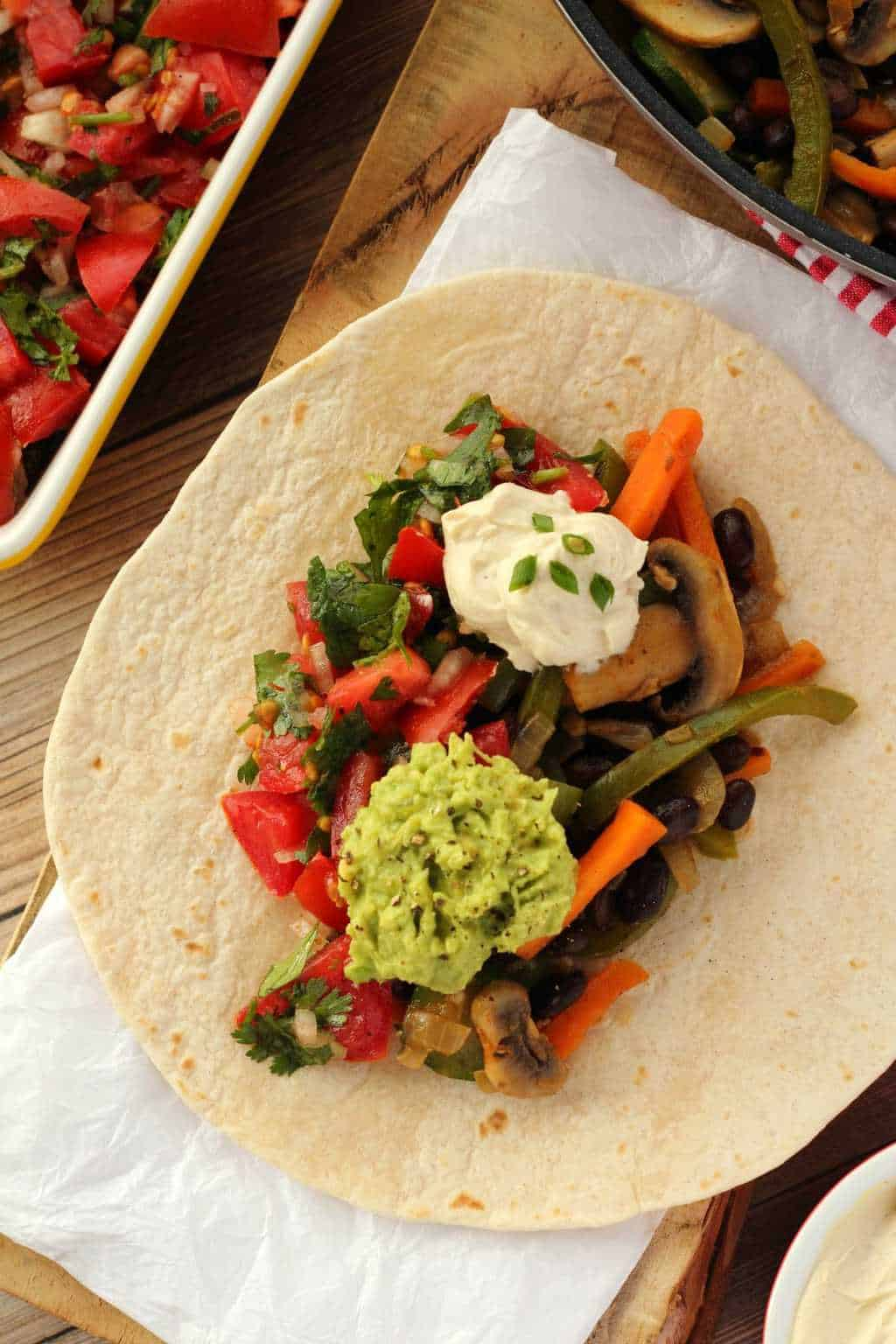 Assembling veggie fajitas on a wooden board.