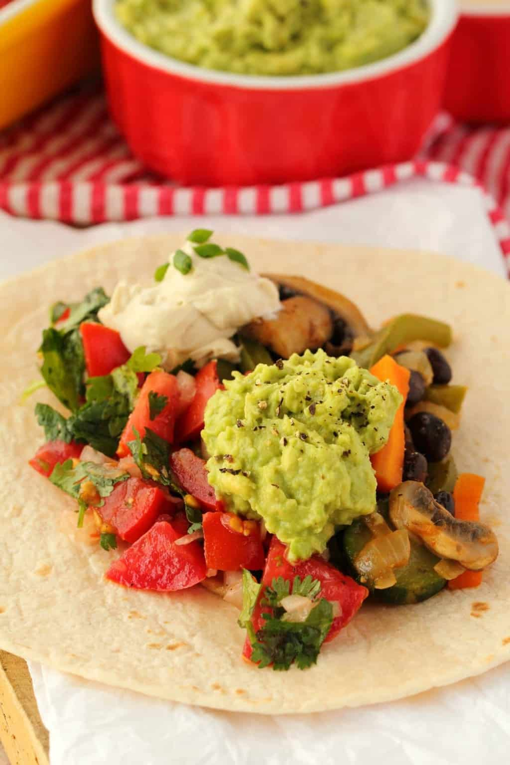 Veggie Fajitas topped with guacamole and sour cream.