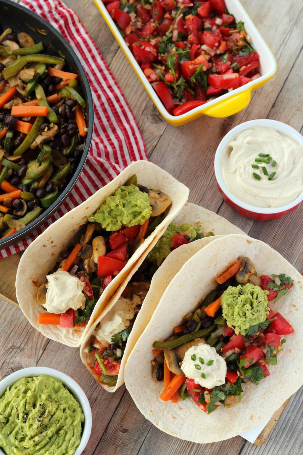 Veggie Fajitas topped with guacamole and vegan sour cream and tomato salsa.