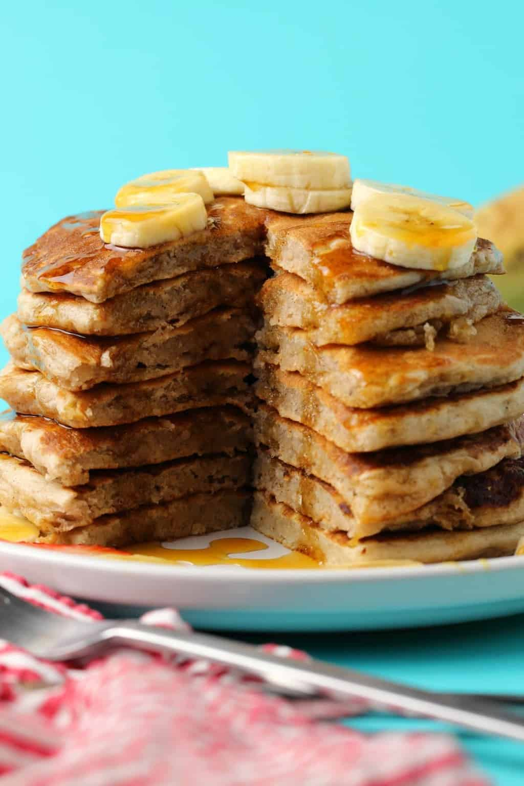 A stack of vegan banana pancakes with a slice cut out to show the centers.
