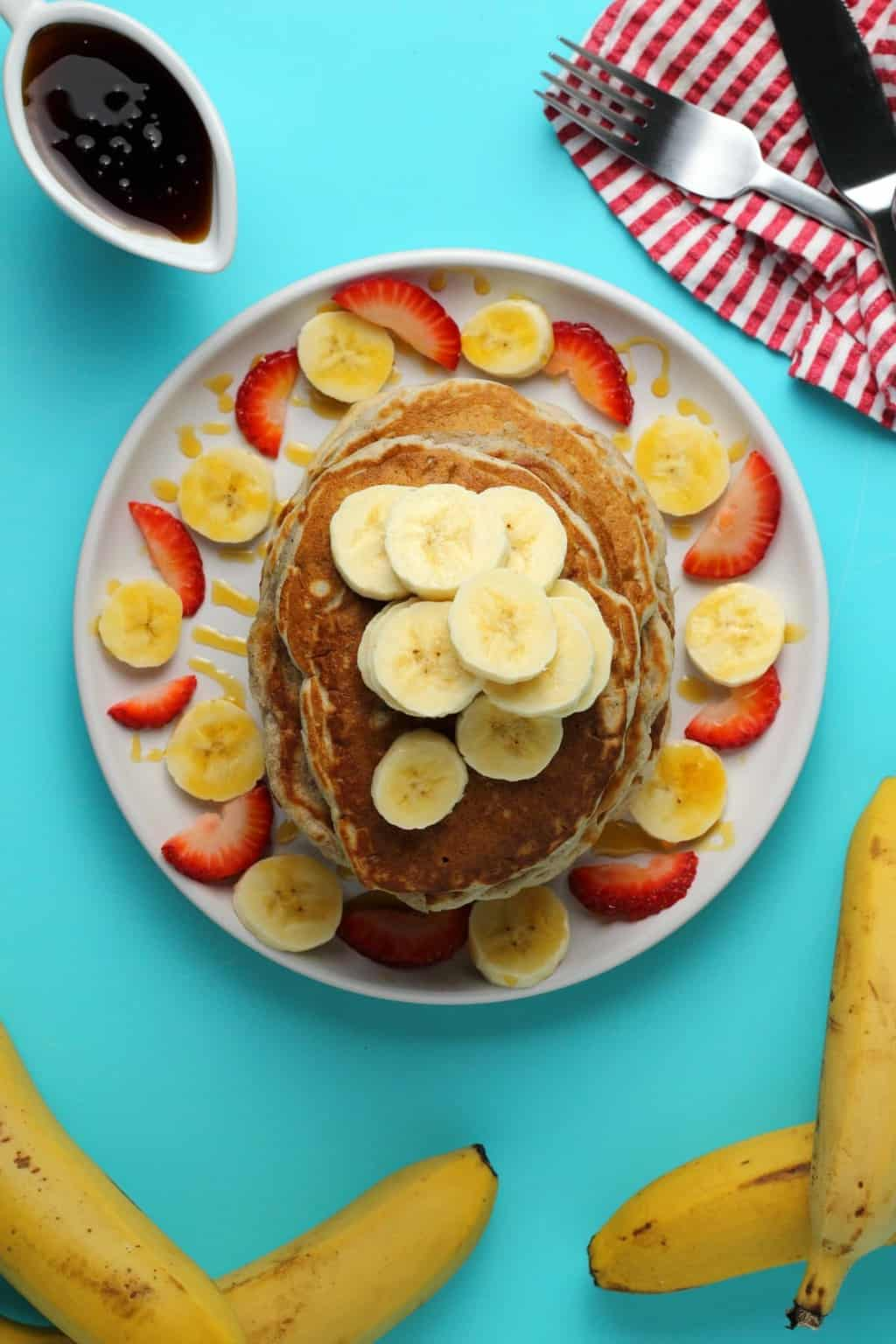 A stack of vegan banana pancakes topped with sliced banana.