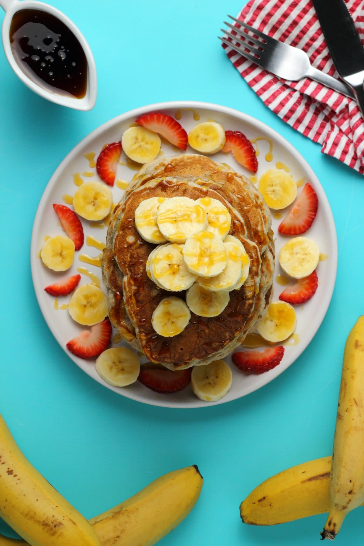 A stack of vegan banana pancakes topped with sliced banana and drizzled with syrup on a white plate.