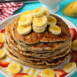 Vegan banana pancakes stacked up on a white plate.