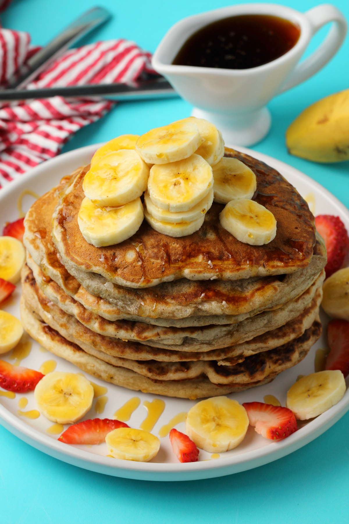 A stack of vegan banana pancakes topped with sliced banana on a white plate.