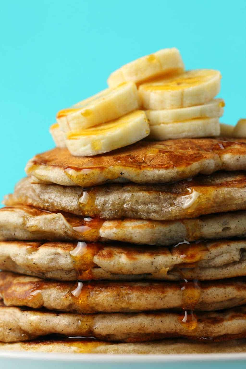 Vegan banana pancakes topped with sliced banana and syrup on a white plate.