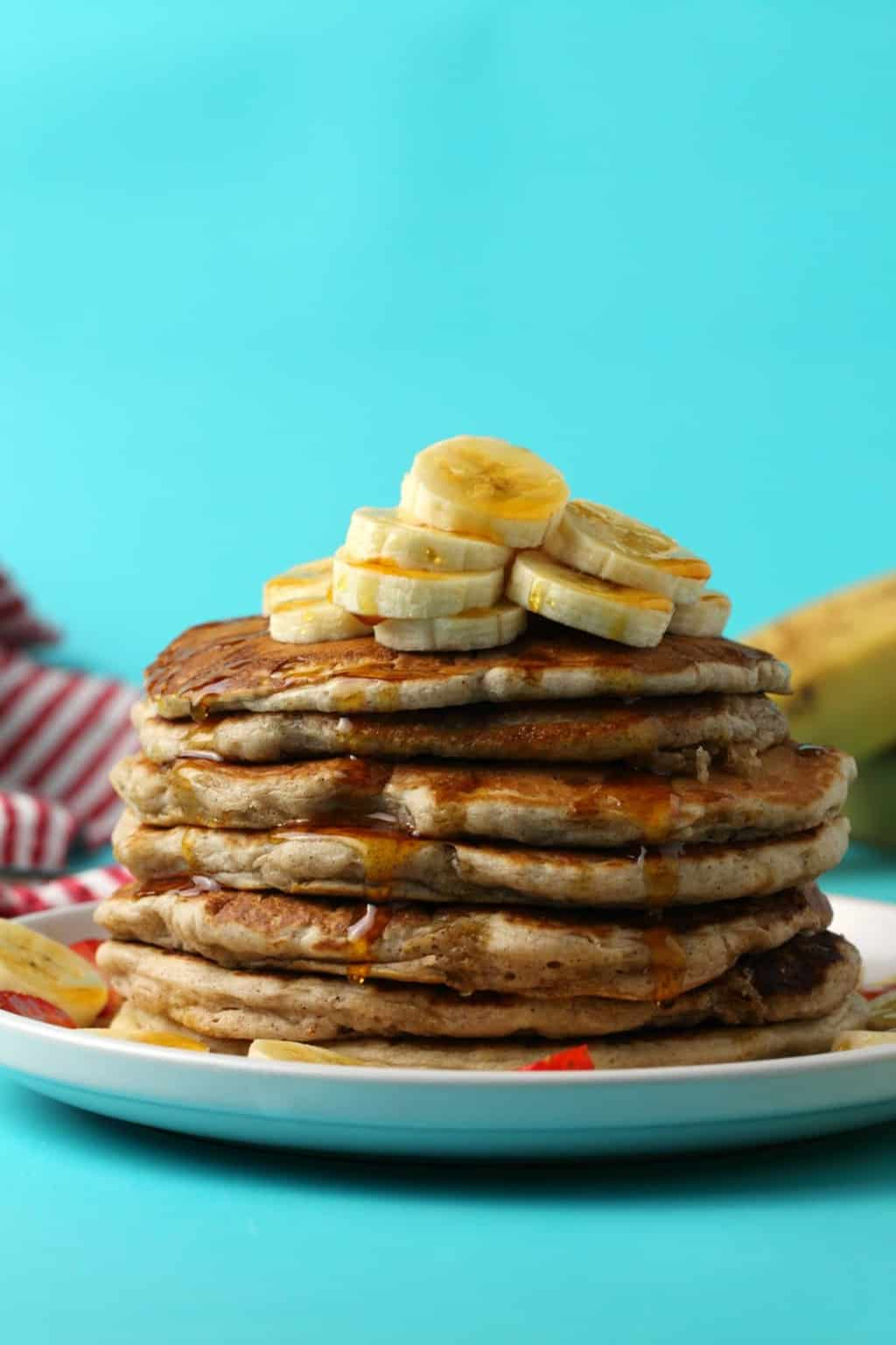 Vegan banana pancakes topped with sliced banana and drizzled with syrup on a white plate.