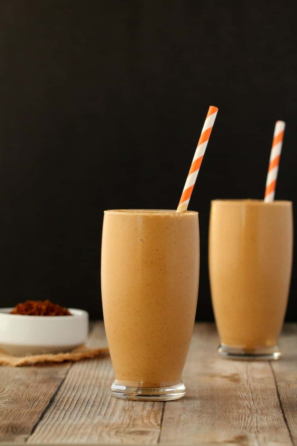 Vegan coffee smoothies in glasses with orange and white striped straws.