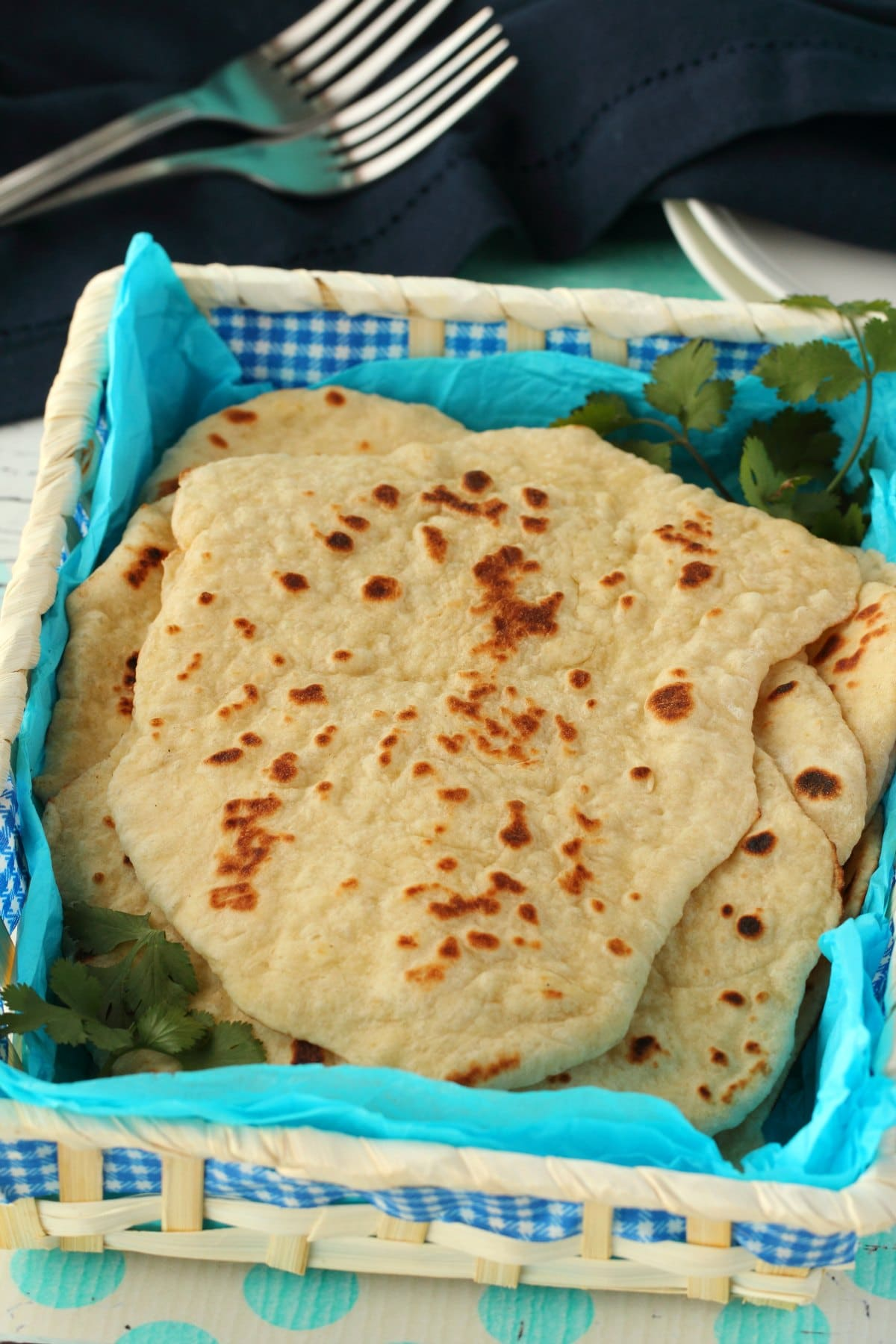Vegan Naan and cilantro in a basket lined with blue paper.