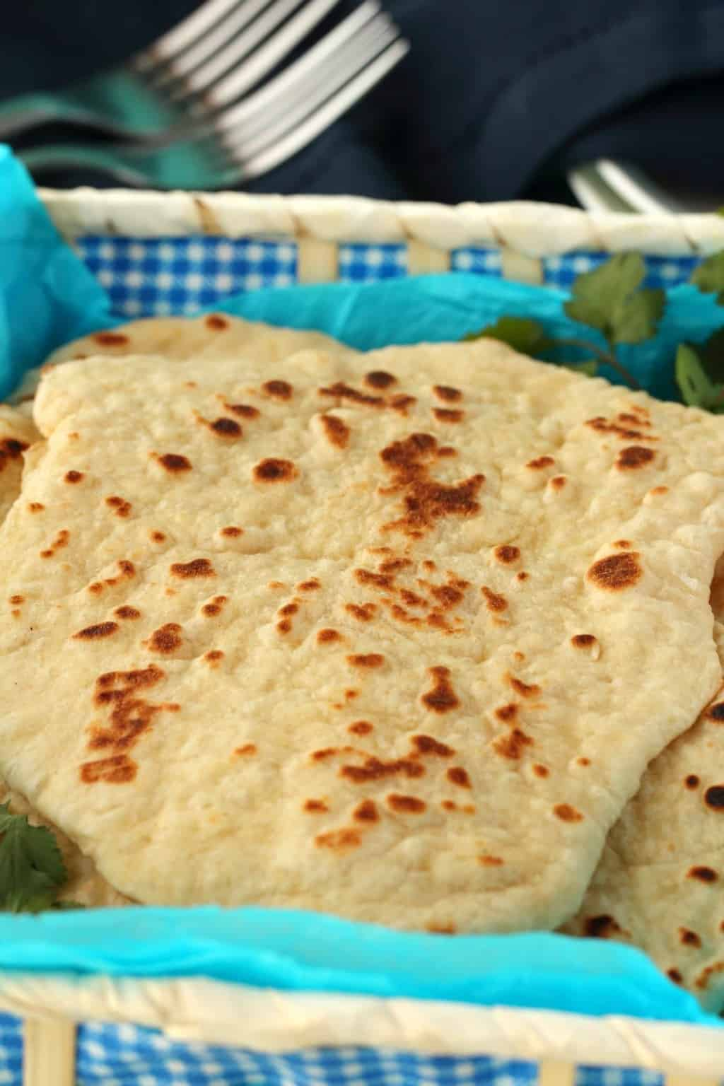 Vegan Naan in a basket lined with blue paper.