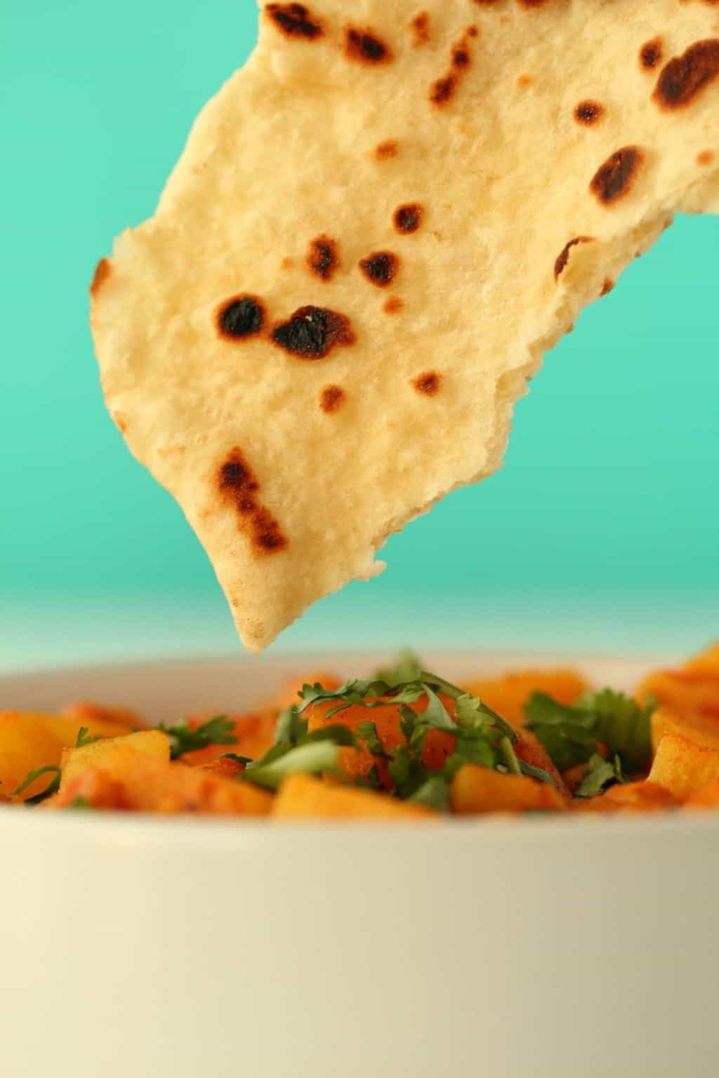 A piece of vegan naan dipping into a bowl of curry.