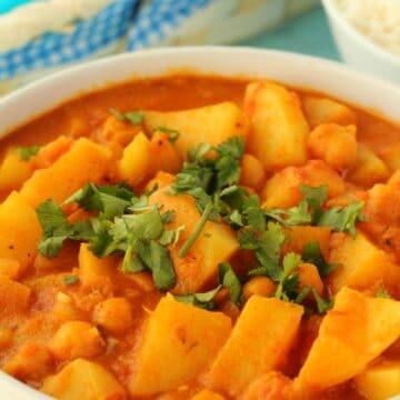 Vegan potato curry in a white bowl.