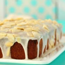 Vegan pound cake topped with glaze and slivered almonds on a white plate.