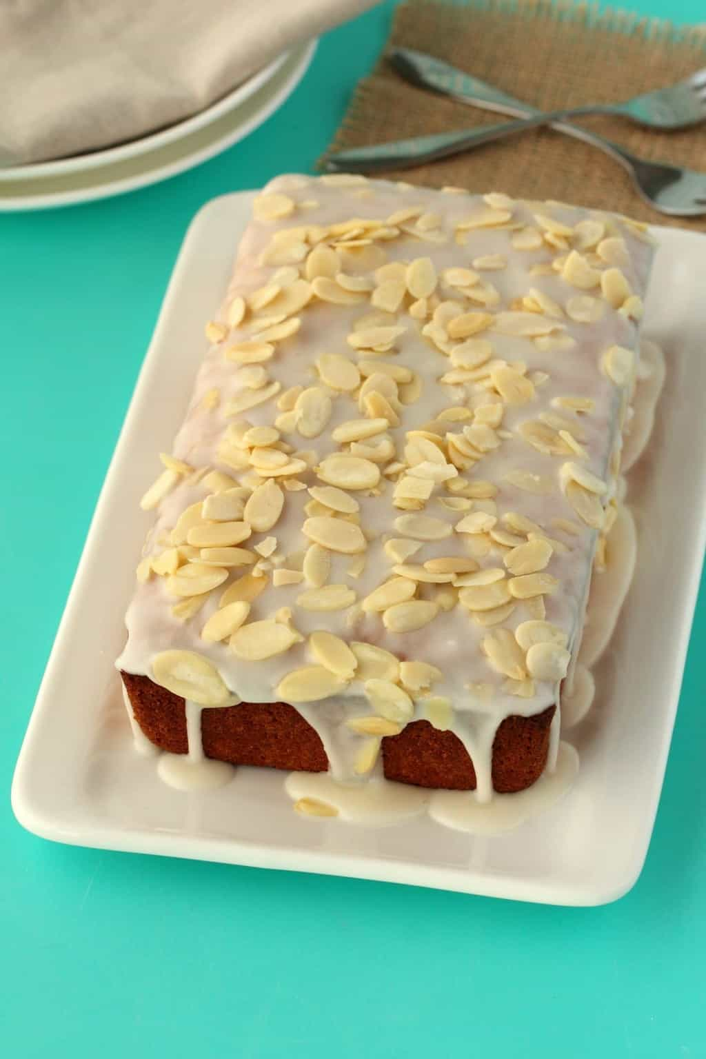 Vegan Pound Cake topped with an almond glaze and almond flakes on a white plate.