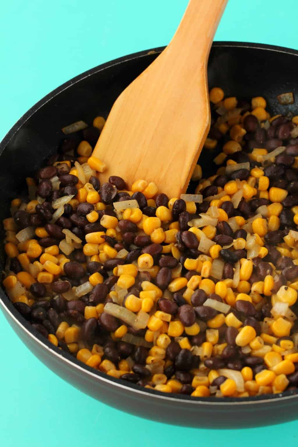 Black bean and corn mix in a frying pan with a wooden spatula.