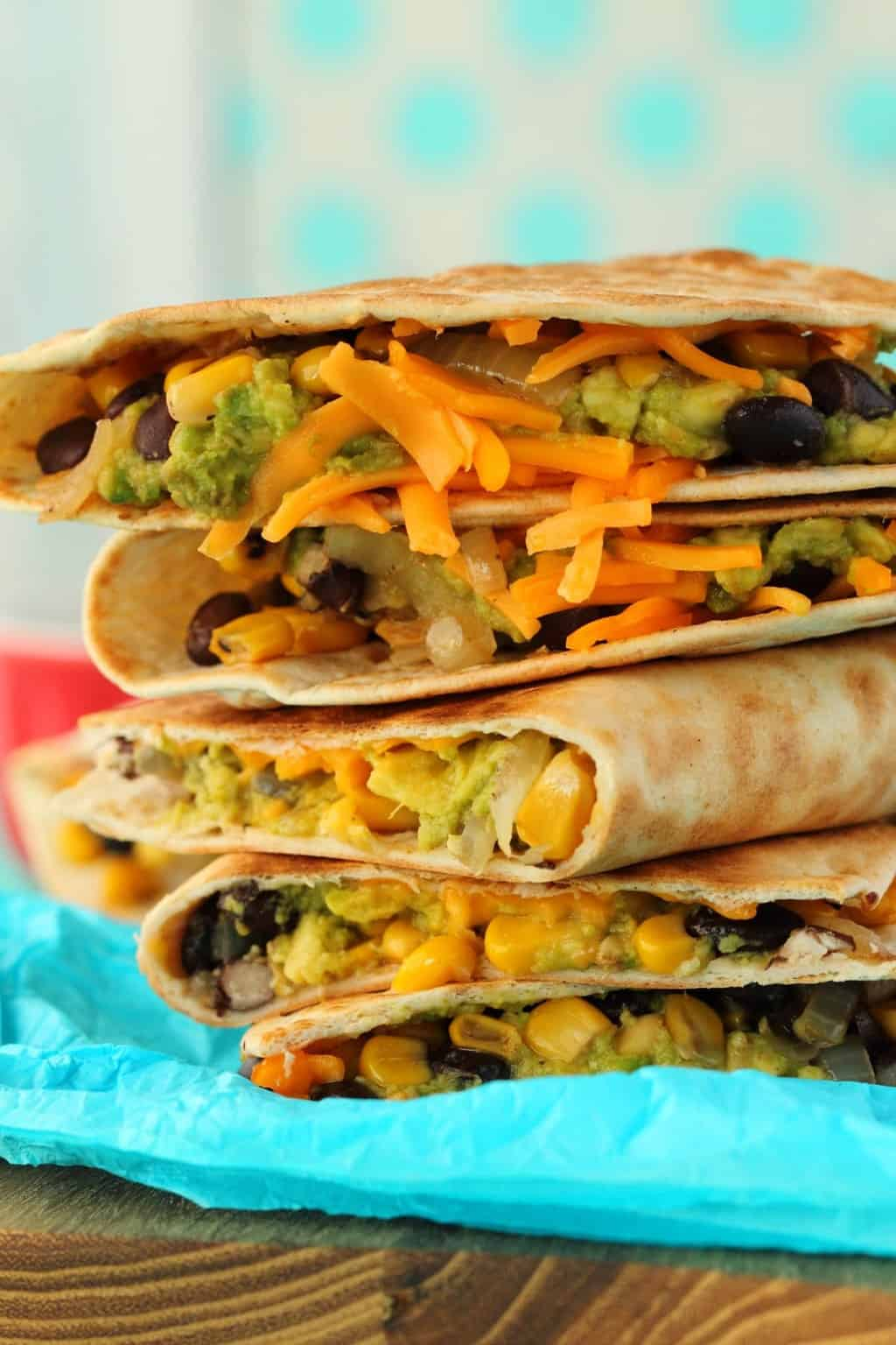 Vegan Quesadillas in a stack on blue paper.