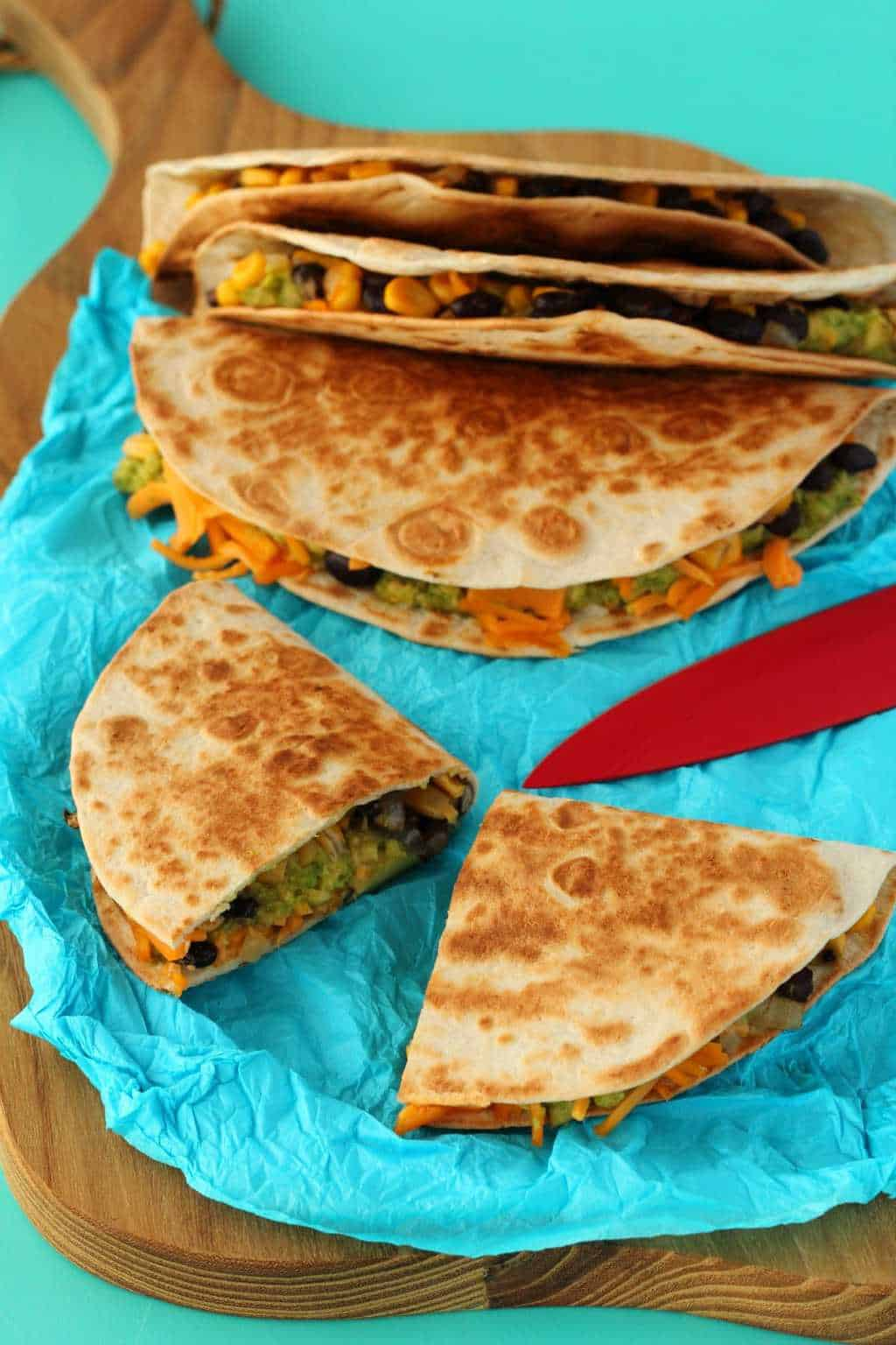 Vegan Quesadillas in a stack with the one in front cut in half.
