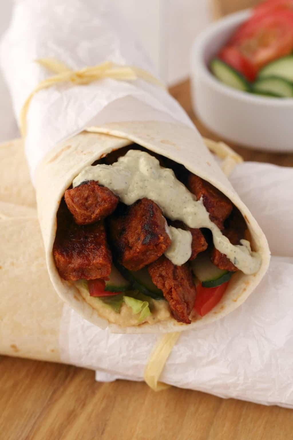 Vegan Shawarma stuffed with seitan, veggies and topped with tzatziki, wrapped with white paper and twine.