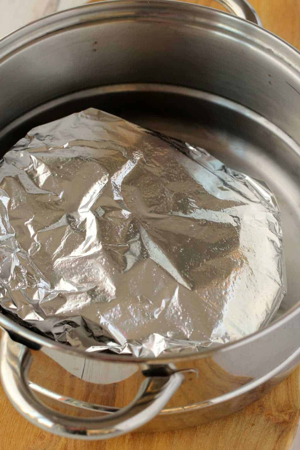 Seitan wrapped in tinfoil and steaming in a steamer pot.