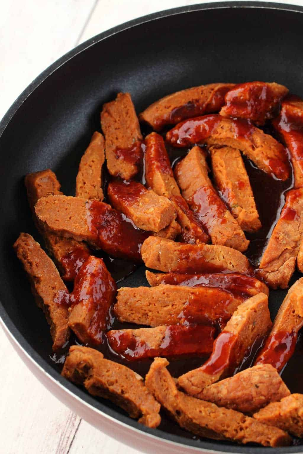 Strips of seitan with marinade sauce poured over them in a frying pan.