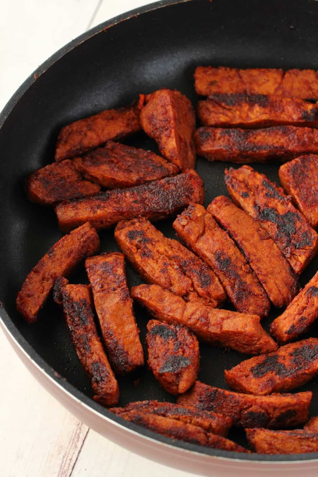 Strips of cooked seitan for vegan shawarmas in a frying pan.