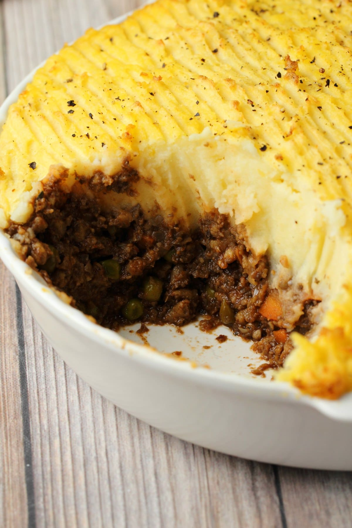 Vegan Shepherd's Pie in a white pie dish, one slice taken out to show the center.