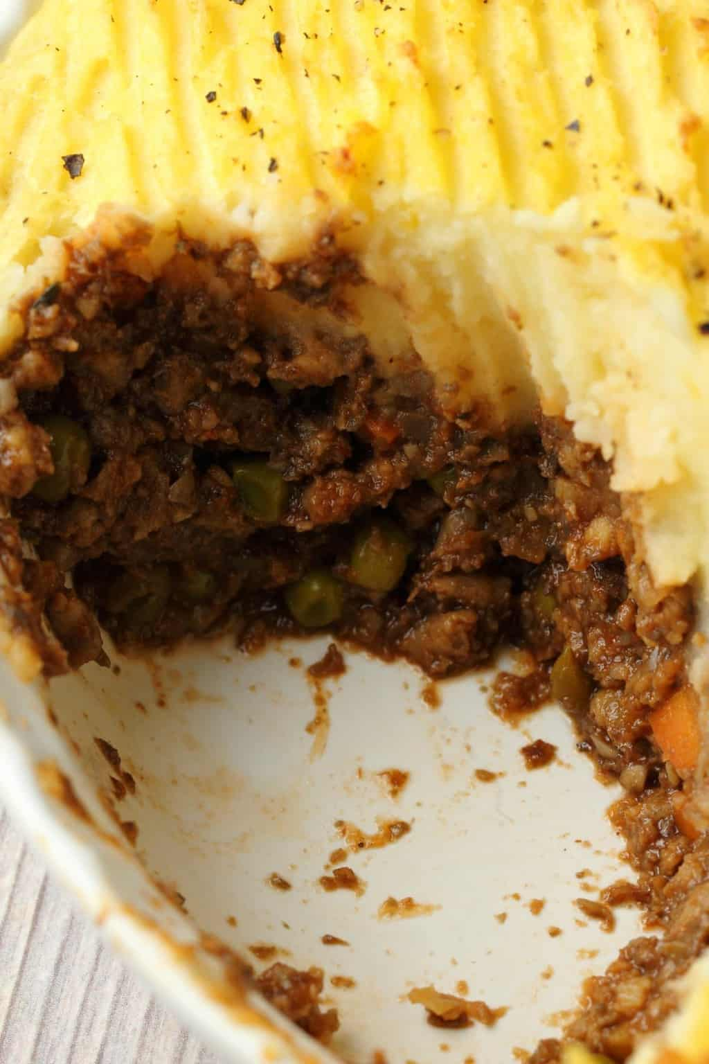 Vegan Shepherd's Pie in a white pie dish, one slice removed to show the layers.