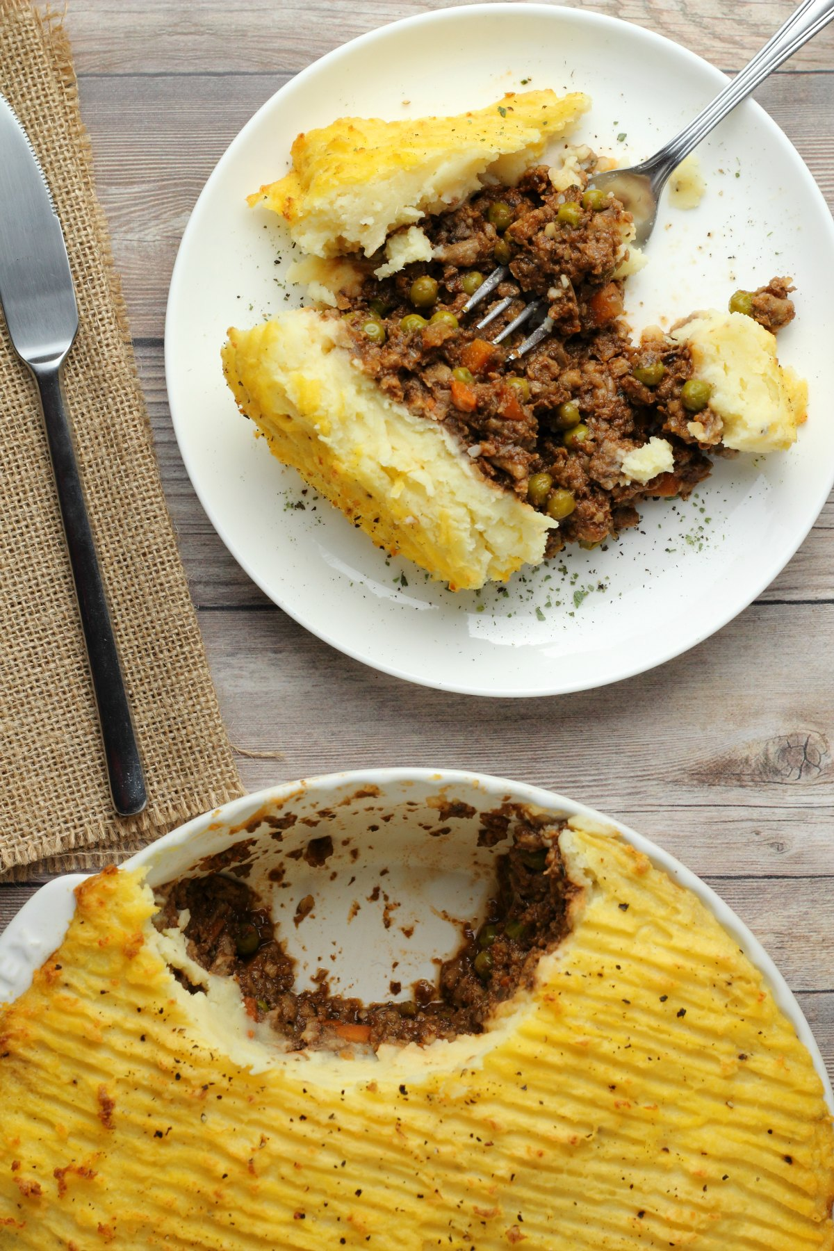 A slice of vegan shepherd's pie on a white plate with a fork.