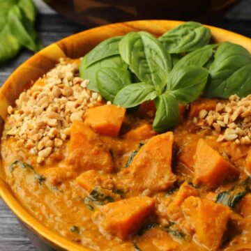 Vegan sweet potato curry with fresh basil in a wooden bowl.