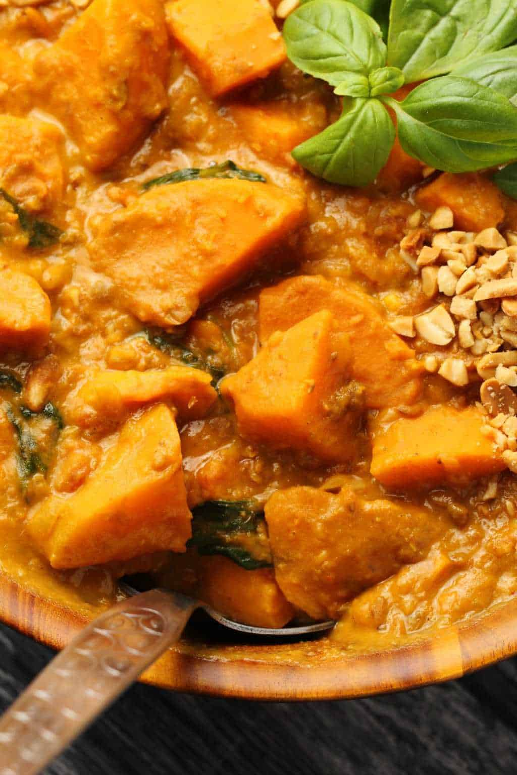 Vegan Sweet Potato Curry topped with fresh basil leaves and crushed peanuts in a wooden bowl with a spoon.