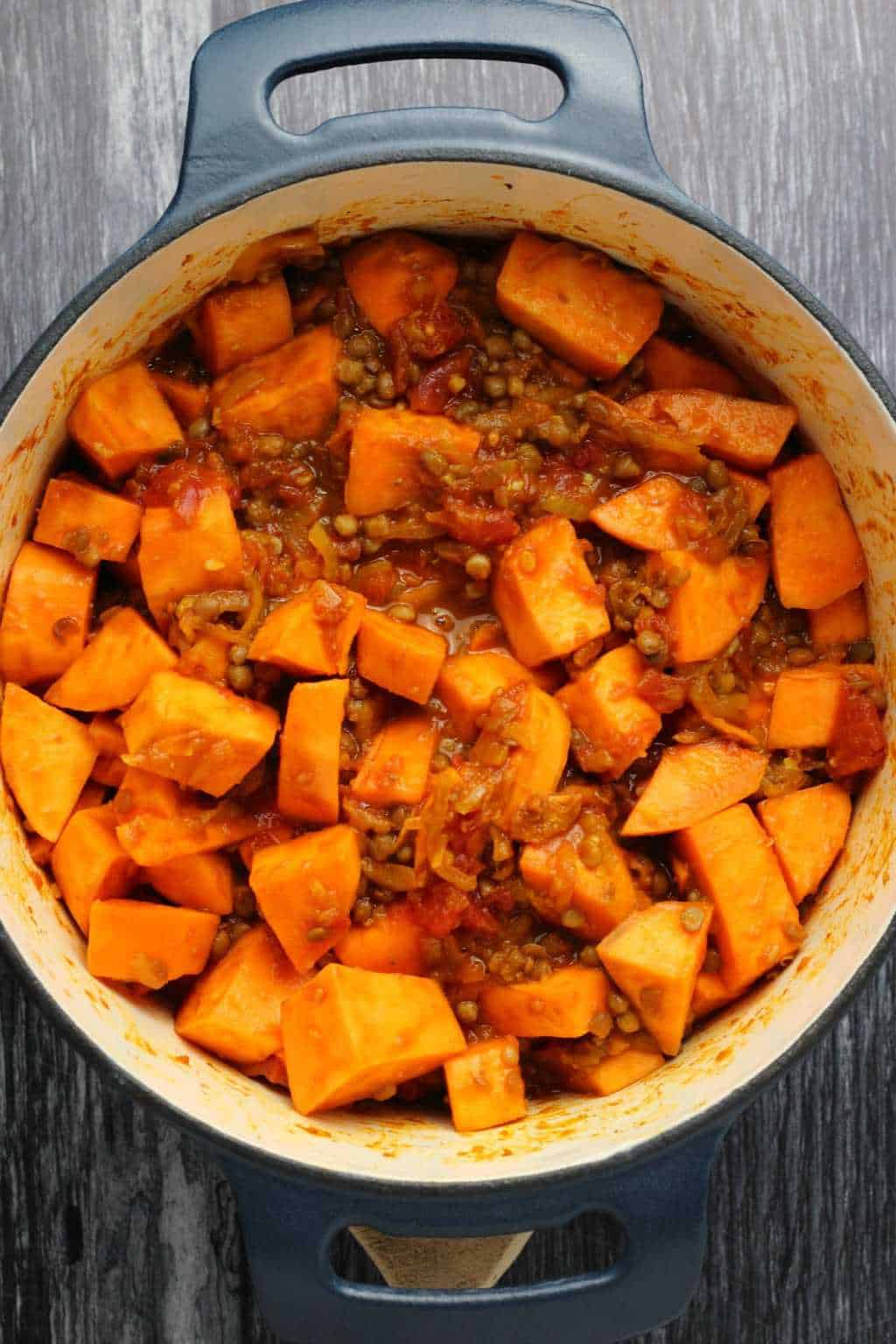 Sweet potato cubes and lentils and spices for a vegan sweet potato curry in a cast iron pot.