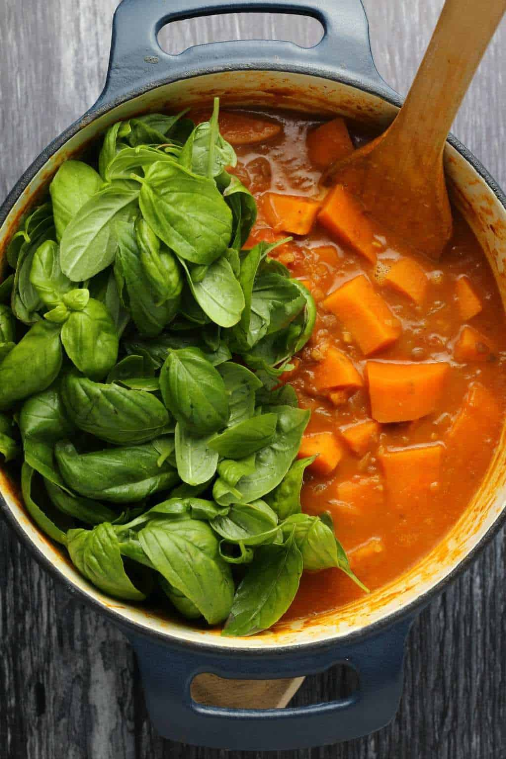 Vegan sweet potato curry and fresh basil leaves about to be stirred in, in a cast iron pot with a wooden spoon.