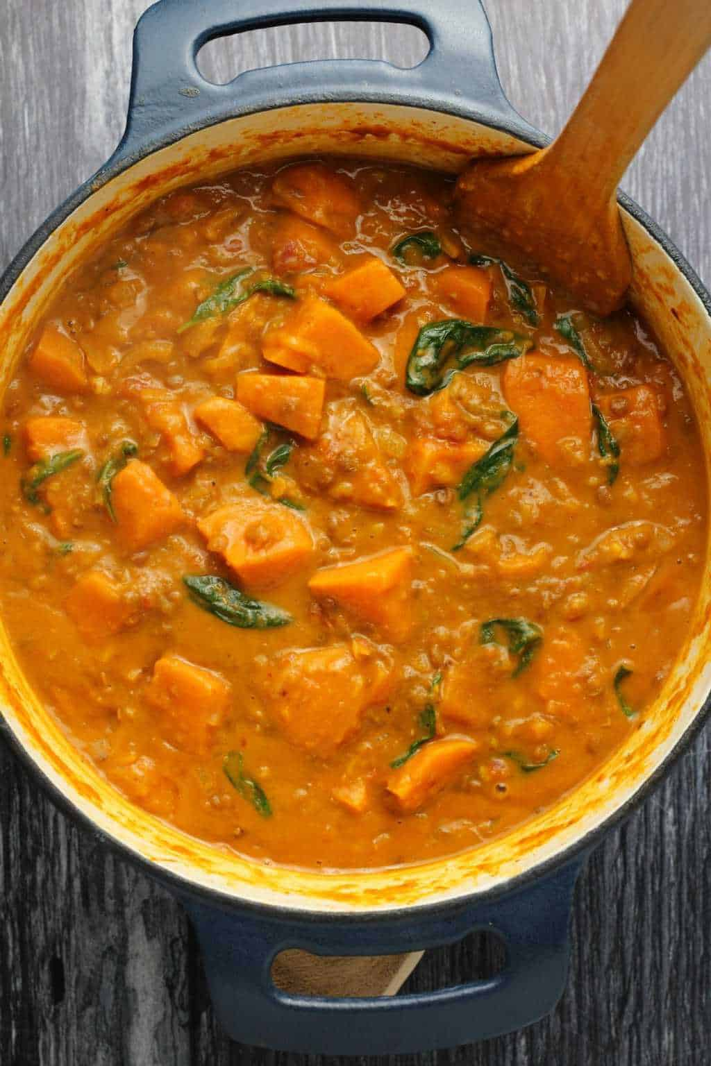 Vegan Sweet Potato Curry in a cast iron pot with a wooden spoon.
