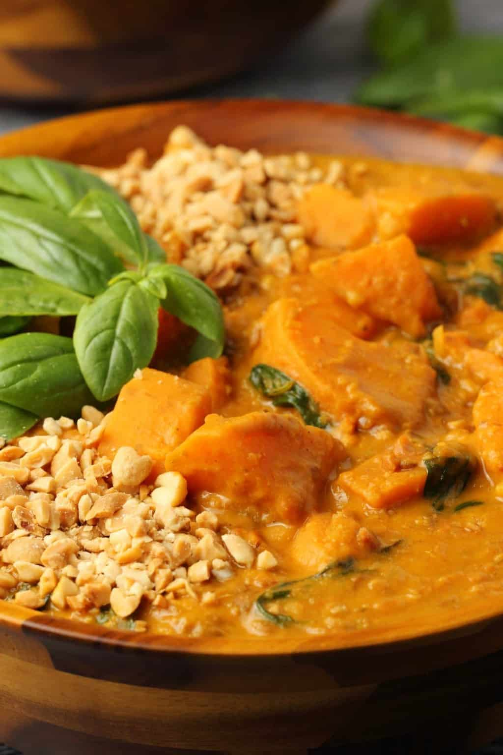 Vegan Sweet Potato Curry topped with fresh basil leaves and crushed peanuts in a wooden bowl.