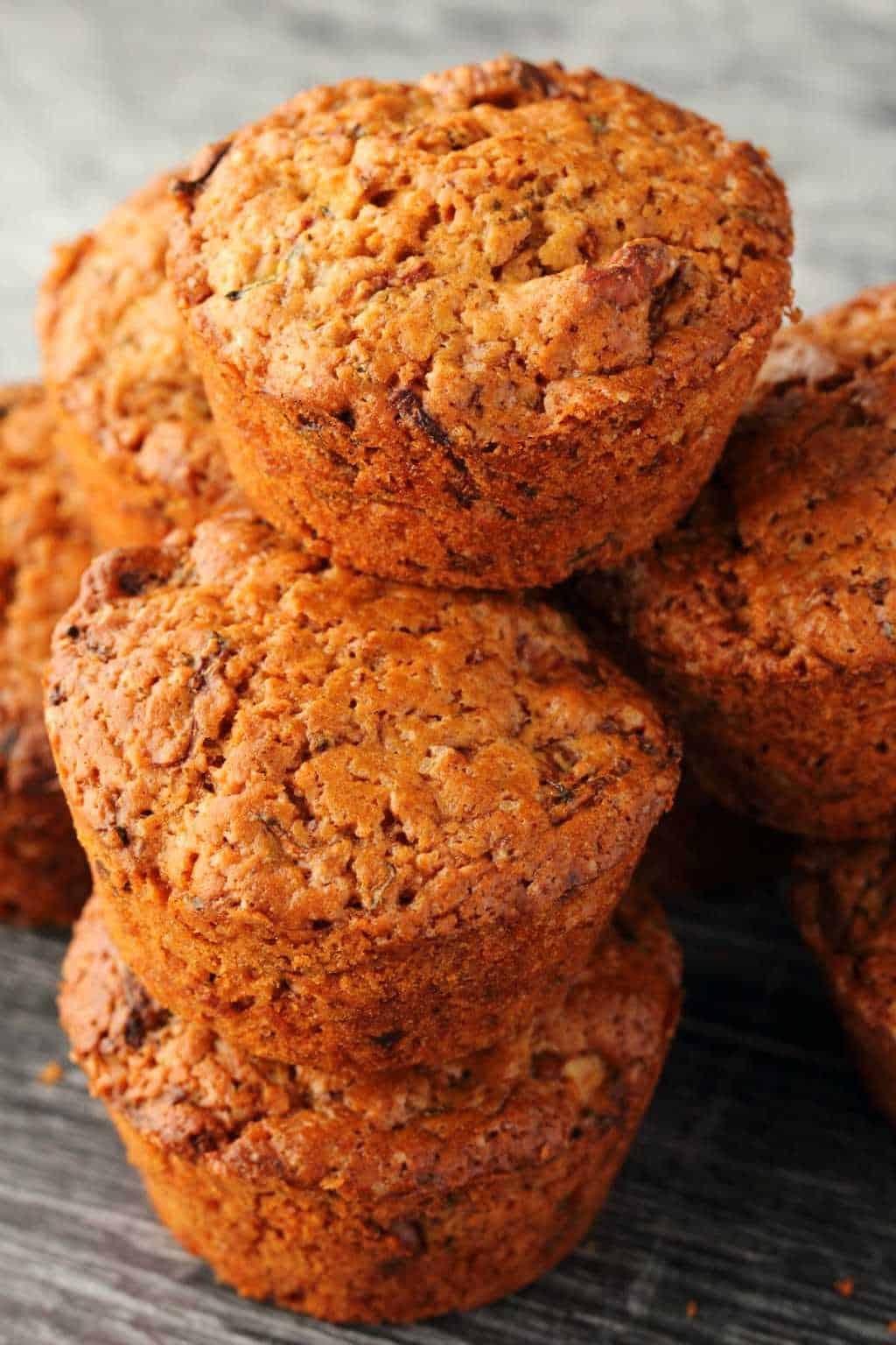 Vegan Zucchini Muffins in a stack against a dark background.