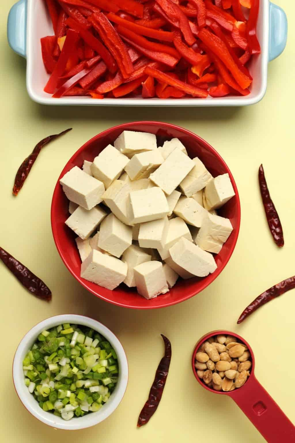 Ingredients for kung pao tofu, cubes of tofu in a bowl, sliced red peppers, dried chilies, chopped spring onion and roasted salted peanuts.