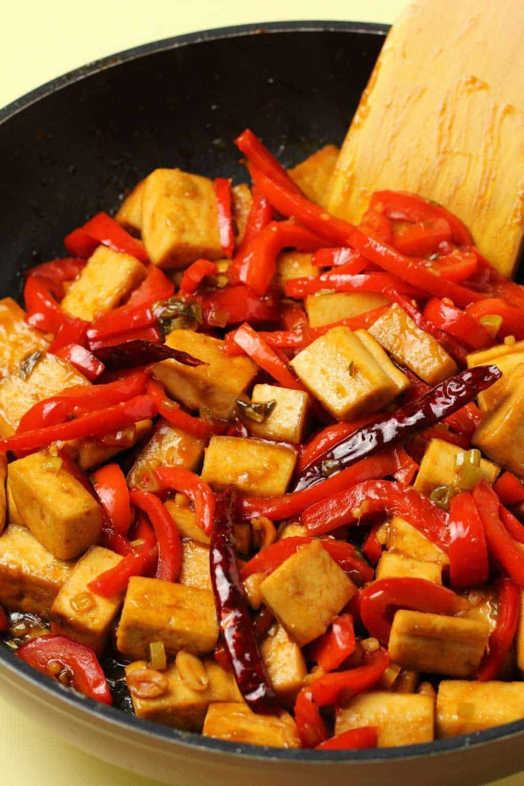 Kung pao tofu in a frying pan with a wooden spatula.