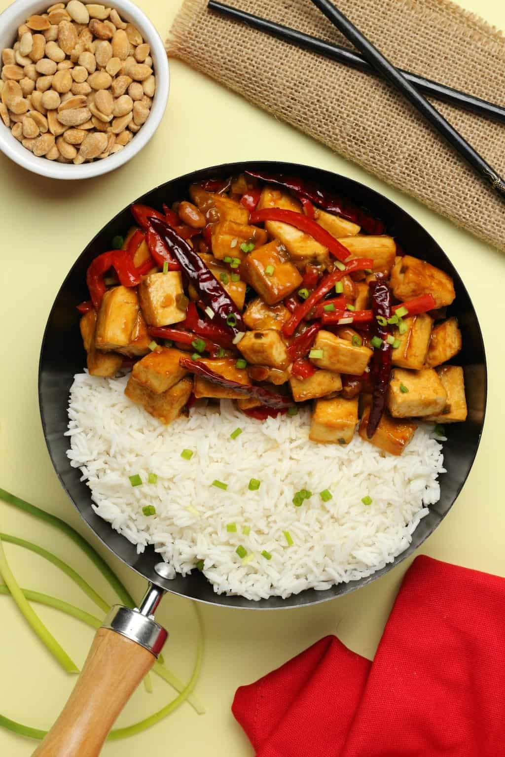 Kung pao tofu in a wok with rice and topped with chopped spring onions.