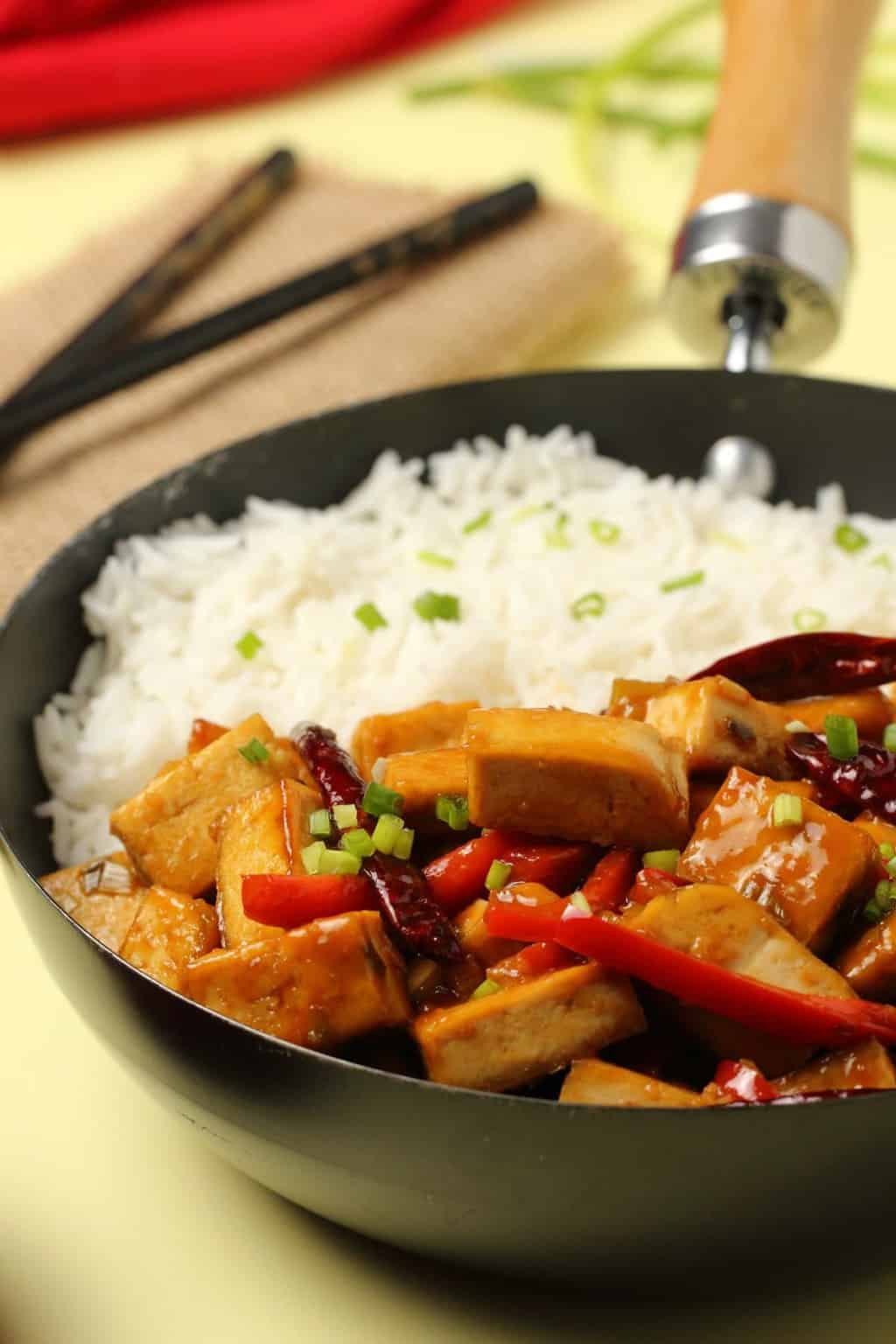 Kung pao tofu served in a wok with basmati rice and topped with chopped spring onions.