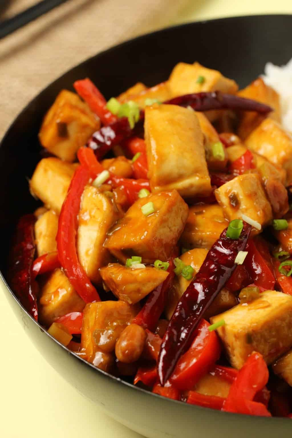 Kung pao tofu served in a wok topped with chopped spring onions.