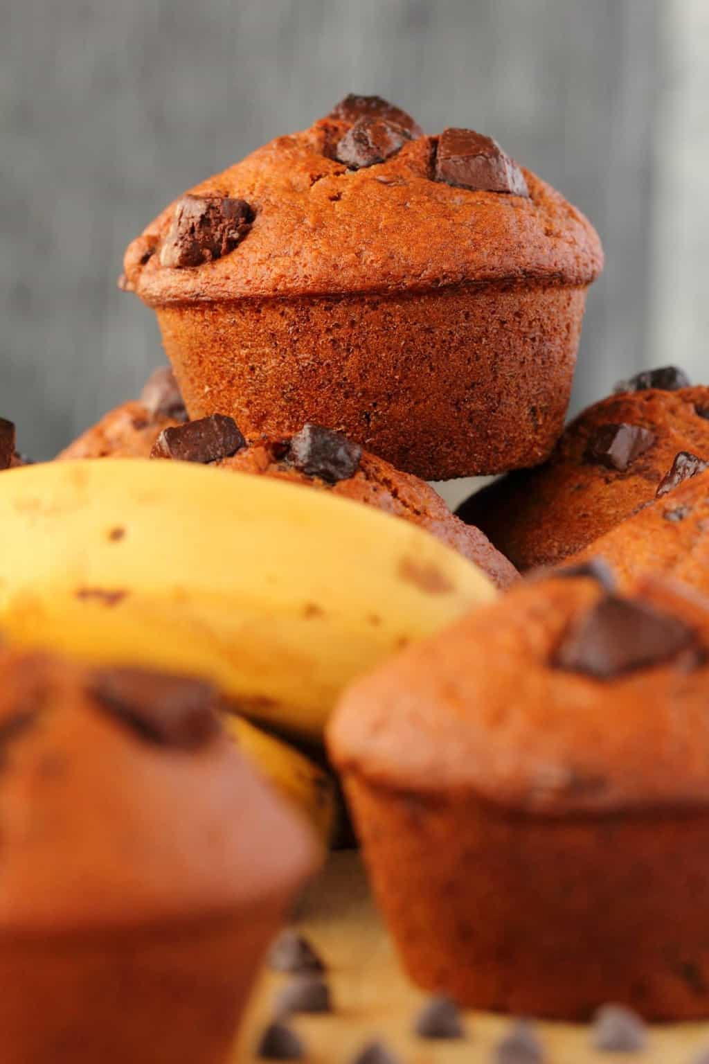 Vegan banana chocolate chip muffins on a wooden board with bananas and chocolate chips.