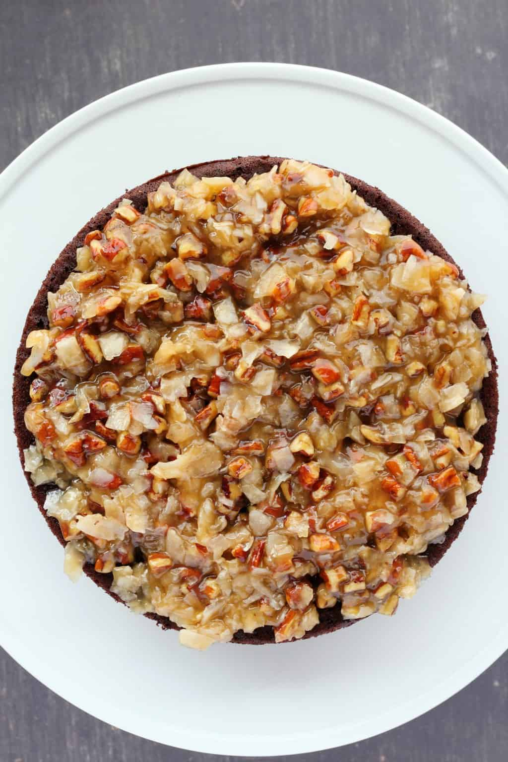 Assembling a vegan German chocolate cake, placing the coconut/pecan filling onto the first layer of chocolate cake.