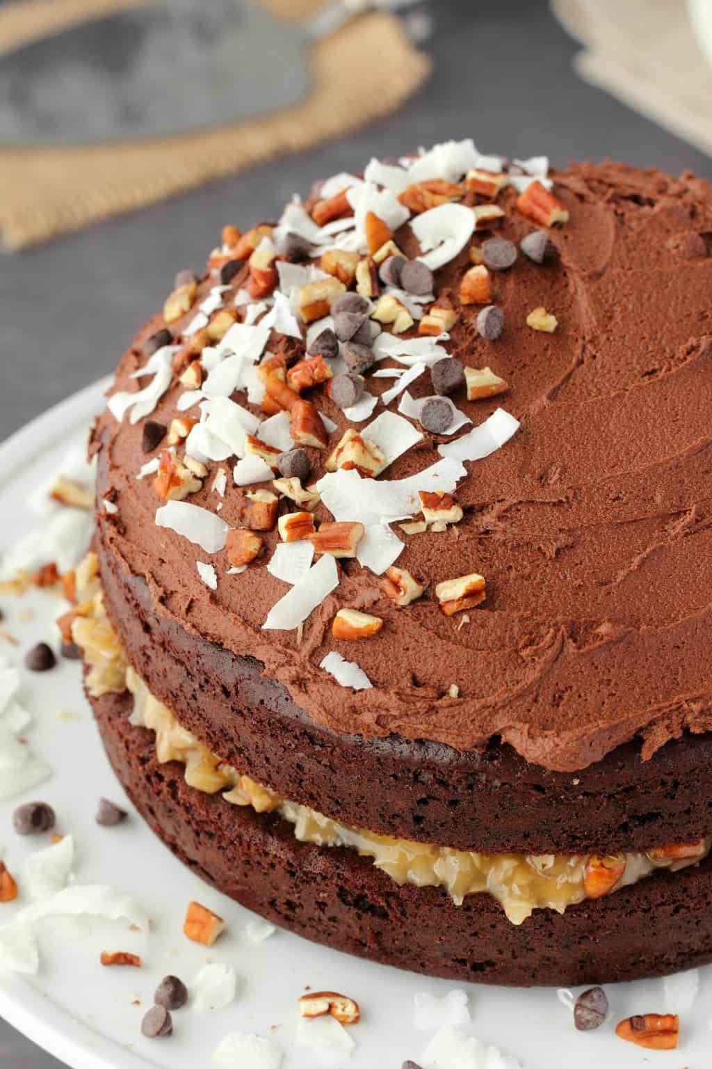 Vegan German chocolate cake decorated with coconut flakes, chocolate chips and chopped pecans, on a white cake stand.