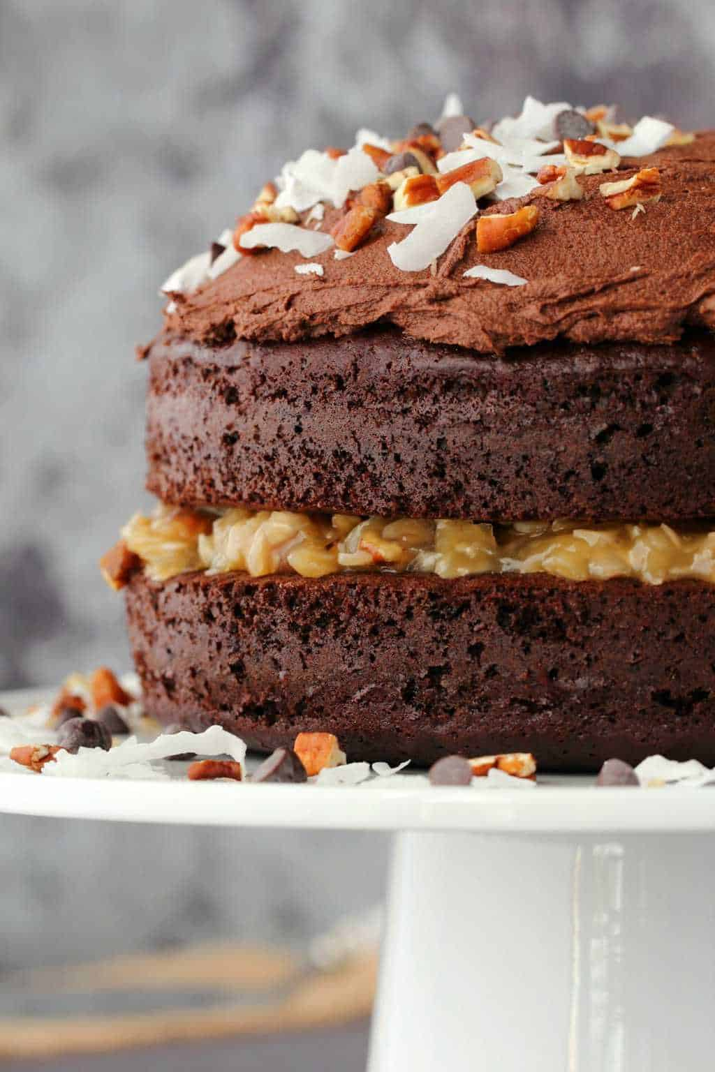 Vegan German chocolate cake decorated with pecans, coconut flakes and chocolate chips, on a white cake stand.